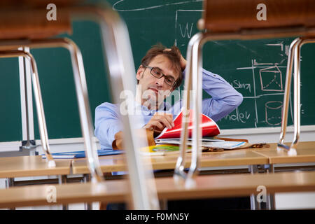 Exhausted teacher in the classroom - Stock Photo