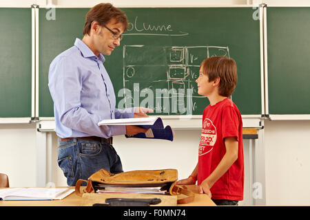 Teacher with pupil in front of blackboard - Stock Photo