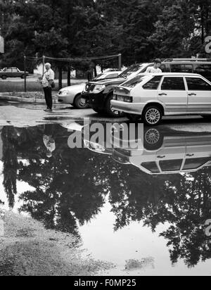 After a heavy rain storm both cars and trees are reflected in a puddle in the road - Stock Photo