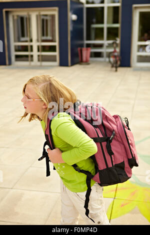 Schoolgirl with a heavy satchel - Stock Photo