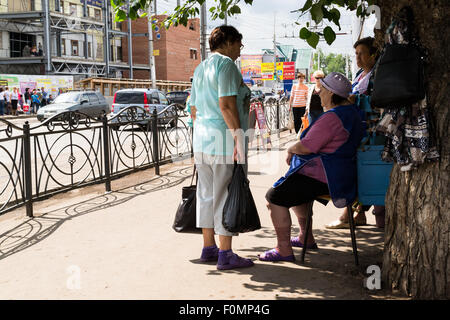 Three women talk on a Russian street corner taking shelter from the hot overhead sun - Stock Photo