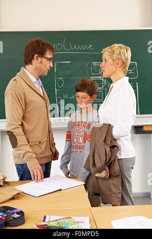 Mother and son talking with the teacher - Stock Photo
