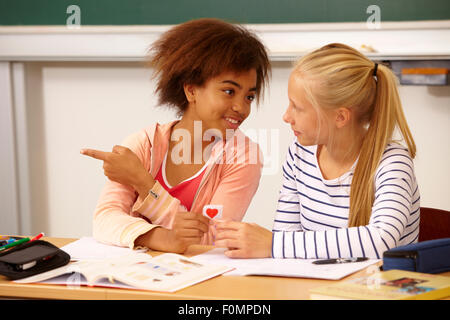 Girl hands over a love letter to her class-mate - Stock Photo