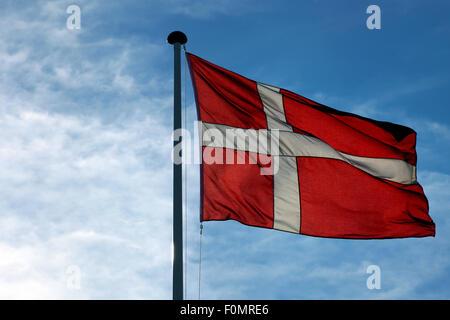 The Danish flag Dannebrog waving against blue sky - Stock Photo