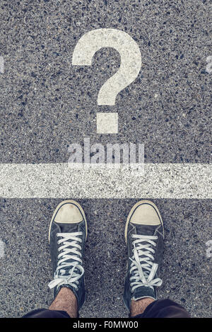 Young man standing on the street questioning, sneakers from above on asphalt road with question mark, urban youth - Stock Photo