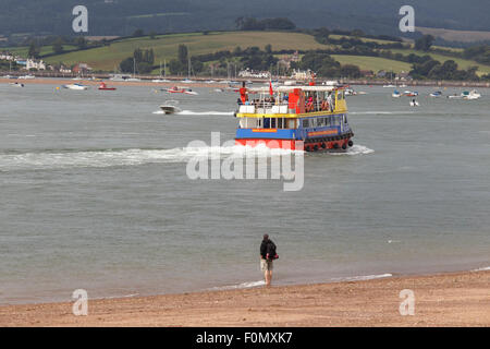 'Pride of Exmouth' ferry, watched from beach by man, cruising into mouth of the river Exe. - Stock Photo