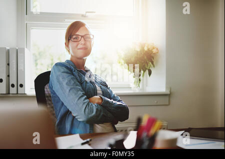 Confident Young Office Woman Sitting at her Desk with Arms Crossing Over her Stomach, Smiling at the Camera Against - Stock Photo