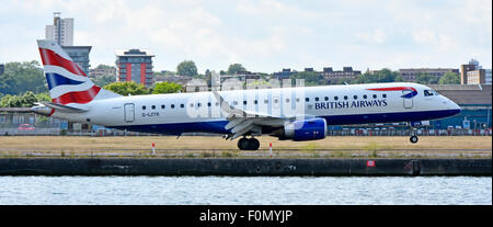 British Airways Cityflyer Embraer 190 G-LCYK landing & touchdown at London City Airport beside old dock waters in - Stock Photo