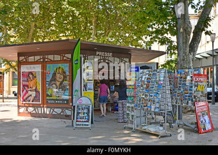 Modern French newspaper kiosk with pavement postcard displays close to the Rotonde Fountain - Stock Photo