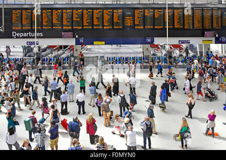 Commuters on busy Waterloo train station concourse with departure board and platform entry exit ticket barriers - Stock Photo