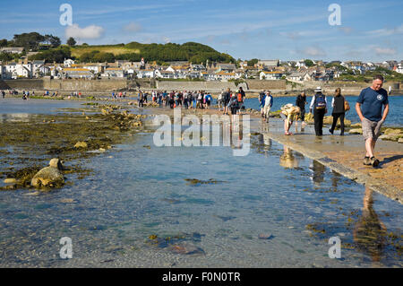 Horizontal view of people crossing the causeway to St Michael's Mount, Cornwall. - Stock Photo