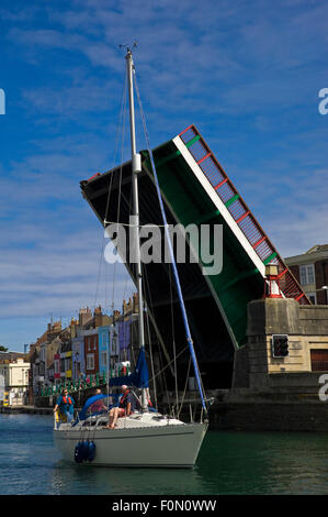 Vertical view of a yacht passing under Town Bridge in Weymouth, Dorset. - Stock Photo