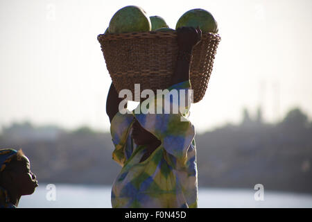 Unidentified Woman carrying vegetables on her head in the streets of Mopti with a young girl - Stock Photo