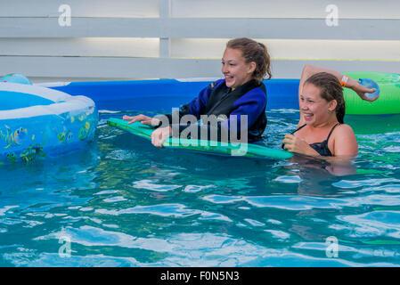 Kids playing in above ground, backyard swimming pool - Stock Photo