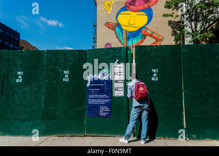New York, NY - 14August 2015 - A passerby peeps through the fence to watch Brazilian twin street artists Os Gemeos - Stock Photo