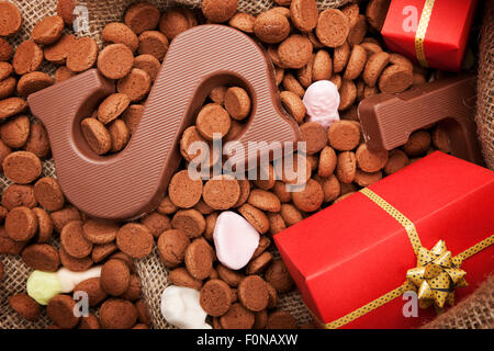 'De zak van Sinterklaas' (St. Nicholas' bag) filled with 'pepernoten', a letter of chocolate and sweets. All part - Stock Photo