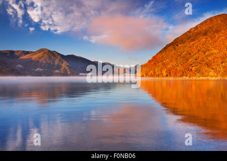 Lake Chuzenji (Chuzenjiko, 中禅寺湖) near Nikko in Japan. Photographed on a beautiful still morning in autumn. - Stock Photo