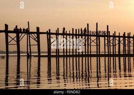 People walking on the U Bein Bridge, Taungthaman Lake, backlight, evening light, sunset, Amarapurna, Divison Mandalay, - Stock Photo