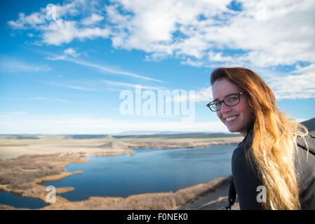 A young woman looks out over Bruneau State Park during a hike. - Stock Photo