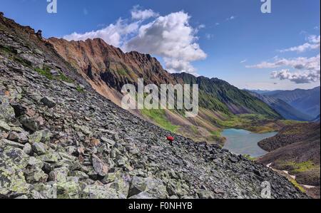 Mountain tourism. The lateral moraine and the woman hiker climbing foot along the moraine. Eastern Sayan. Buryatia - Stock Photo