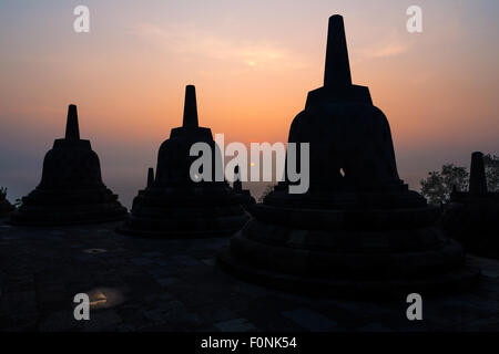 Silhouette's of Stupa's at sunrise at the Unesco world heritage site the Borobudur temple on Java, Indonesia, Asia. - Stock Photo