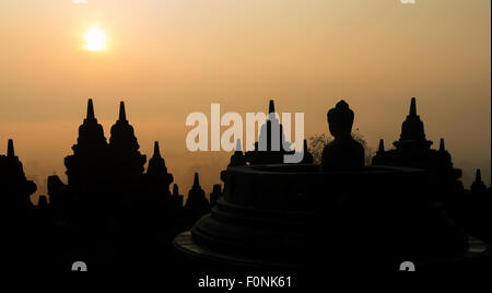 Silhouettes of a Buddha statue at the Unesco world heritage site the Borobudur temple at dawn on the island of Java, - Stock Photo