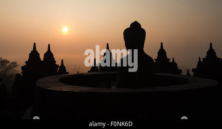 Panorama of a silhouette of a buddha statue at the Unesco world heritage site the Borobudur temple at dawn on the - Stock Photo