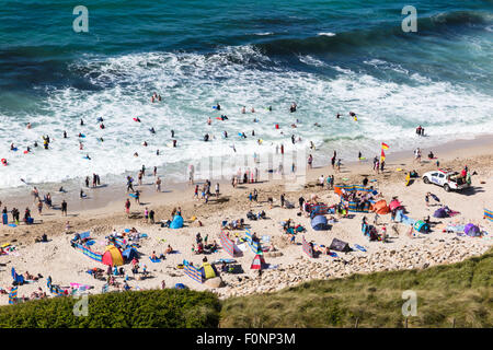 A busy afternoon on Sennen Beach in Cornwall. Sunbathers, surfers and body boarders all enjoy the sunshine and waves - Stock Photo