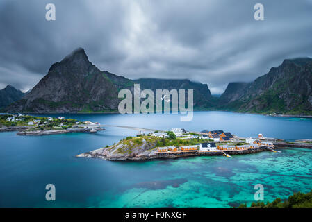 Mount Olstind above the yellow cabins and turquise waters of Sakrisoy fishing village on Lofoten islands in Norway - Stock Photo