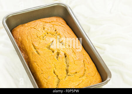 A close-up image of delicious, homemade, moist, freshly baked banana bread on a white cloth. - Stock Photo