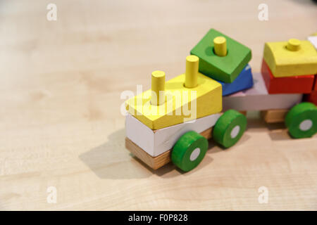 Close up view of multicolored wooden train toy puzzle, on wooden table background. - Stock Photo