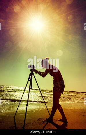 Pretty woman is a professional photographer with dslr camera and tripod - Stock Photo