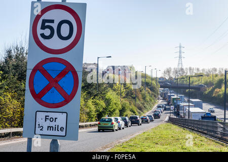 50 mph speed limit sign and a No Stopping road sign with traffic congestion on the A454, Black Country Route, Bentley, - Stock Photo