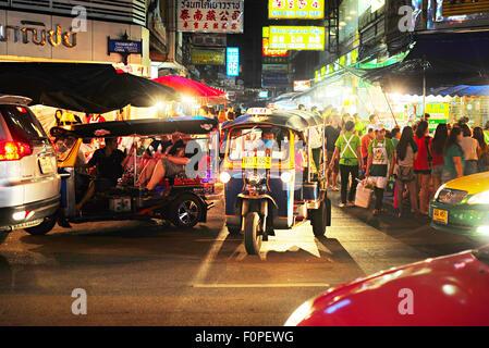 Bangkok taxi 'Tuk-tuk' with passengers in Chinatown street. - Stock Photo