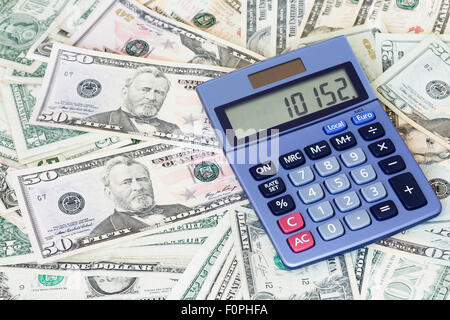US money background with a blue calculator on top - Stock Photo