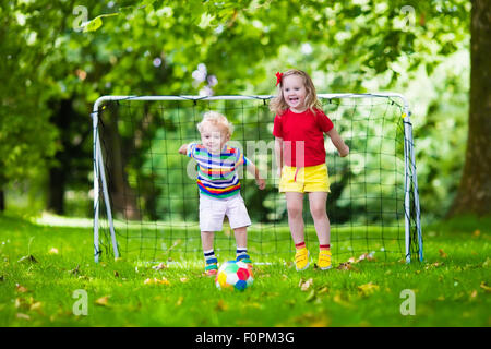 Two happy children playing European football outdoors in school yard. Kids play soccer. Active sport for preschool - Stock Photo