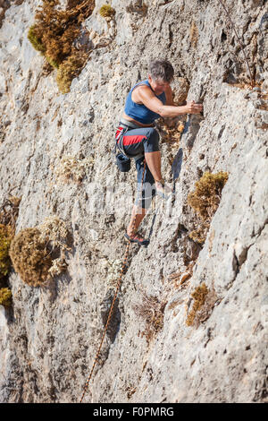 Senior female rock climber on a face of a cliff - Stock Photo