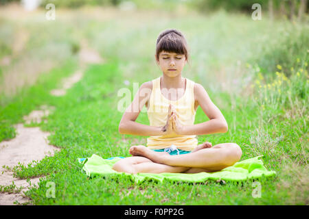 little girl relaxing in yoga pose on grass in a park stock