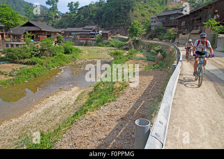 Cycling through a Dong village in China's Guizhou province - Stock Photo