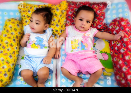 Portrait of twin baby brothers happily sharing a bed together and playing and smiling with copy space - Stock Photo