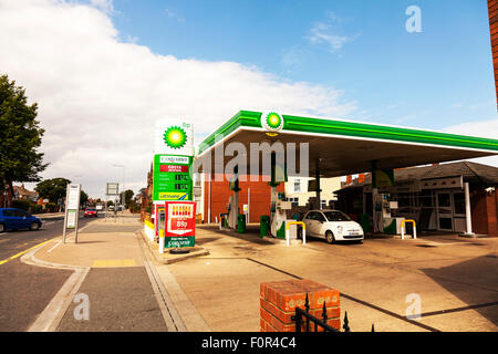 BP petrol station British Petroleum pumps for gas and diesel fuel forecourt lady filling up car UK England - Stock Photo
