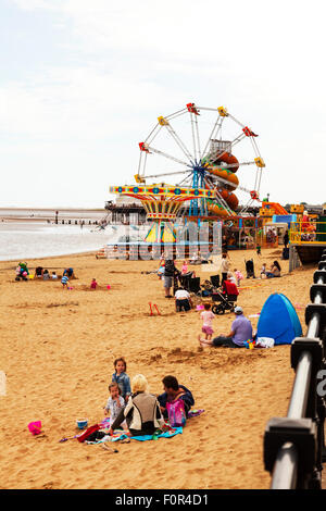 Cleethorpes seafront beach kids playing in sand in front of amusements UK town towns England coast coastal sea - Stock Photo