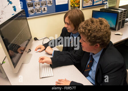 Male secondary school pupils using Information technology, Surrey, UK. - Stock Photo