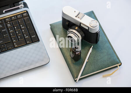 35mm vintage photocamera on diary with film, pen and notebook - Stock Photo