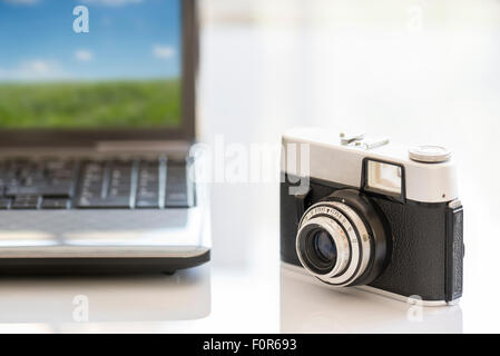 35mm vintage photocamera on white table near notebook - Stock Photo