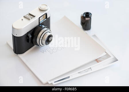 35mm vintage photocamera on wedding book with print and film - Stock Photo