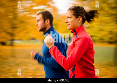 Panning photo of young couple jogging together in nature - Stock Photo