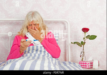 Sick woman sitting in bed looking worried at thermometer with tissues, a rose and washcloth - Stock Photo