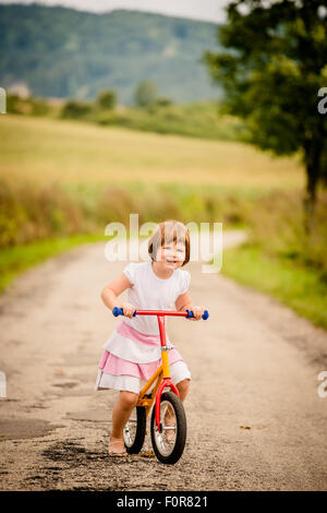 Little child driving her firs bicycle on rural road outdor in nature - Stock Photo