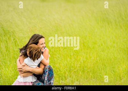Mother and child are hugging and embracing outdoor in nature - Stock Photo